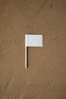Bovenaanzicht van witte vlag op bruin zand