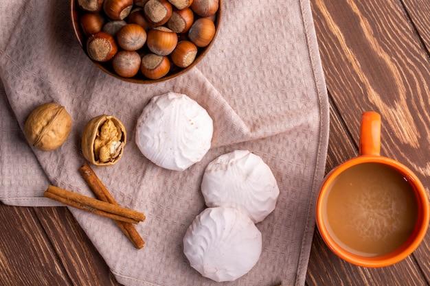 Bovenaanzicht van witte zephyr marshmallows hazelnoten in een kom en een mok cacaodrank op een houten