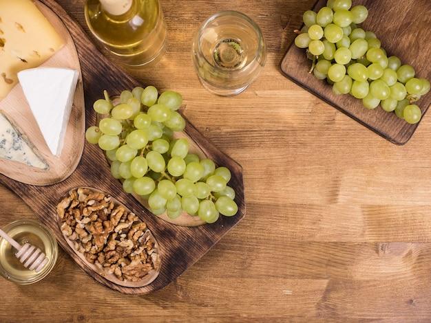 Bovenaanzicht van wolnoten naast verse druiven op houten plaat in een vintage restaurant. glas witte wijn.