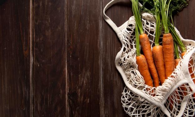 Bovenaanzicht van wortelen in tas met kopie ruimte