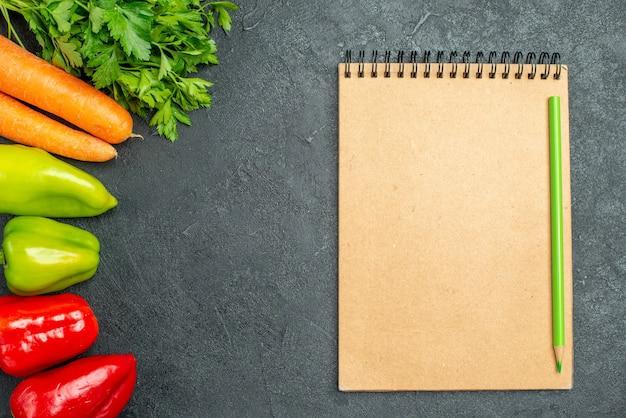 Bovenaanzicht van wortelgroenten en paprika's aan de linkerkant met notitieblok aan de zijkant op de donkergrijze tafel