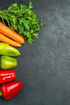 Bovenaanzicht van worteltjesgroenten en paprika's aan de linkerkant op de donkergrijze tafel