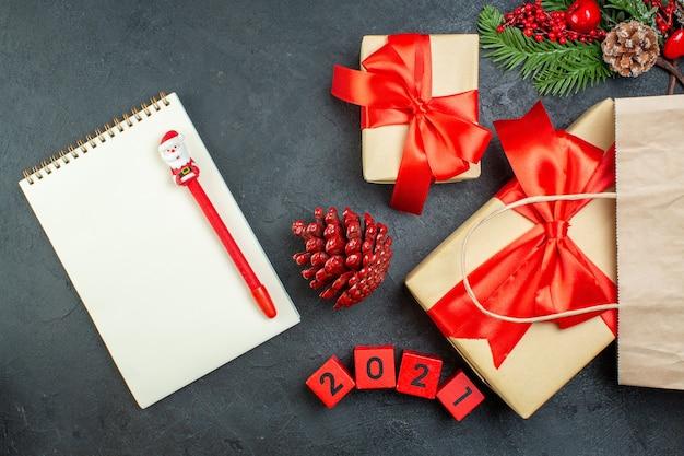 Bovenaanzicht van xsmas stemming met kegels van naaldbomen en cadeau fir takken naast notebook op donkere tafel