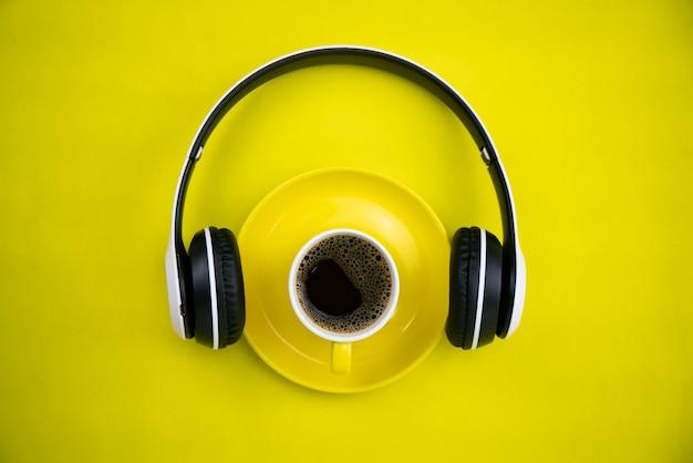Bovenaanzicht van yellpw koffiekopje met hoofdtelefoon op geel papier achtergrond.