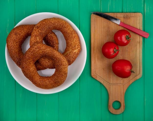 Bovenaanzicht van zachte en sesam bagels op een plaat met verse tomaten op een houten keukenplank met mes op een groene houten achtergrond
