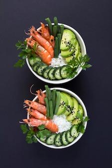 Bovenaanzicht van zak salade met rode garnalen en groene groente in de witte kommen op de zwarte achtergrond. locatie verticaal.