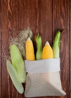 Bovenaanzicht van zak vol met likdoorns met maïs schelp en zijde op hout