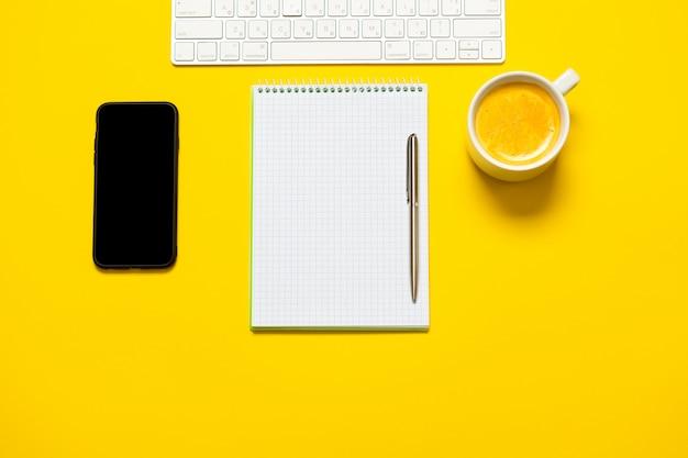 Bovenaanzicht van zakelijke werkplek met kopje koffie, lege werkruimte op gele tafel.