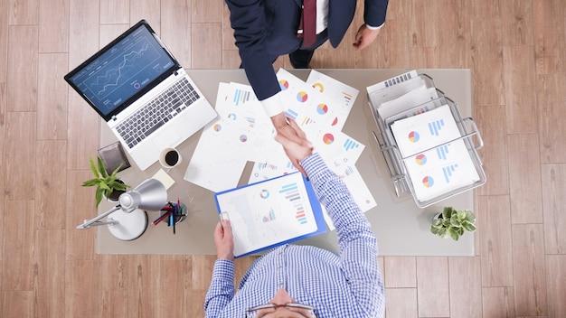 Bovenaanzicht van zakenlieden die handen schudden na zakelijk partnerschap over bedrijf