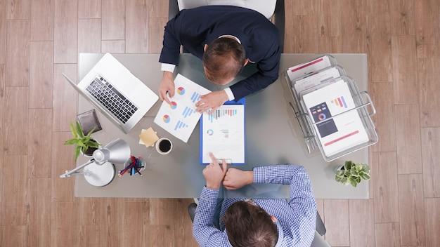 Bovenaanzicht van zakenlieden die managementstatistieken analyseren en bedrijfsstrategie plannen