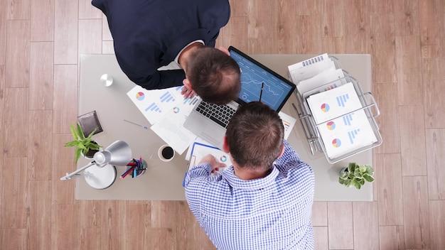 Bovenaanzicht van zakenlieden die managementstatistieken analyseren met behulp van laptop