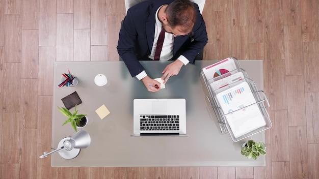 Bovenaanzicht van zakenman die aan de telefoon praat met partner die bedrijfswinst schrijft op plaknotities