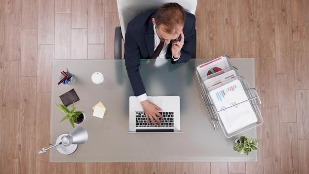 Bovenaanzicht van zakenman die bedrijfswinst bespreekt met partner aan de telefoon terwijl hij bedrijfsstatistieken typt