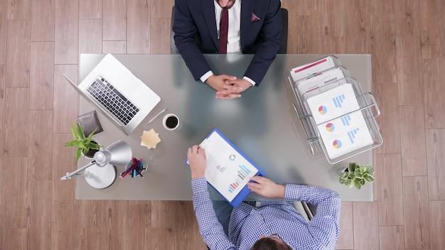 Bovenaanzicht van zakenman die financiële documenten analyseert en bedrijfsstrategie bespreekt
