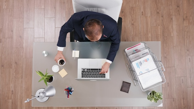 Bovenaanzicht van zakenman die kopje koffie vasthoudt tijdens het typen van bedrijfsstatistieken