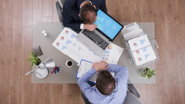 Bovenaanzicht van zakenman die managementstrategiepresentatie toont aan partner die bedrijfsstatistieken bespreekt tijdens zakelijke bijeenkomst. zakenlieden die werken bij financiële grafieken in startbureau
