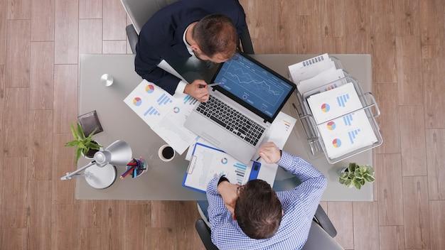 Bovenaanzicht van zakenman die managementstrategiepresentatie toont aan partner