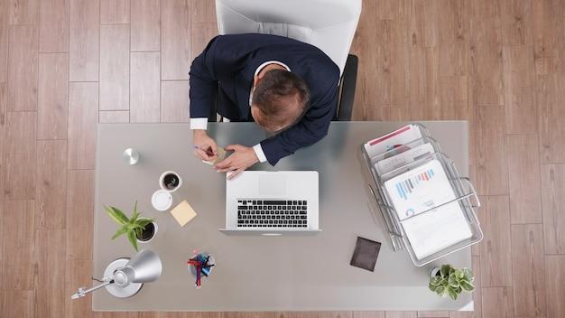 Bovenaanzicht van zakenman die online winst schrijft op plaknotities die werken bij managementstrategie