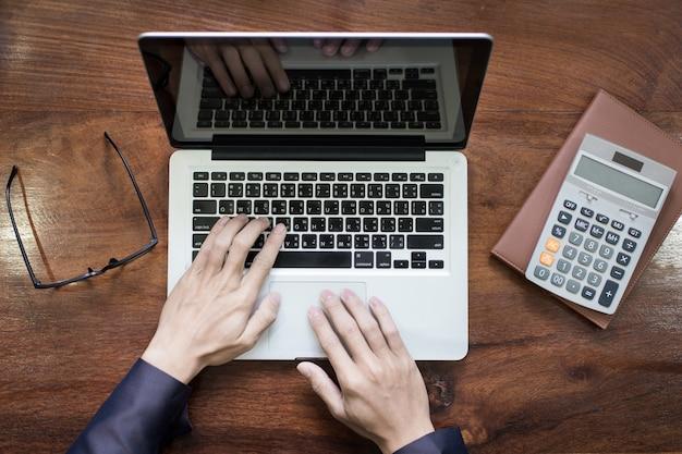 Bovenaanzicht van zakenman handen werken op laptop of tablet pc op houten bureau.