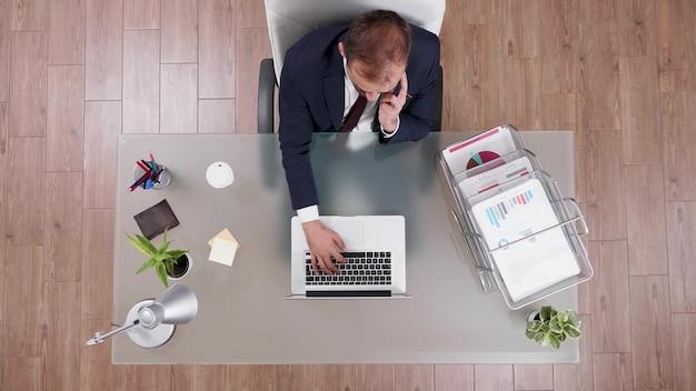 Bovenaanzicht van zakenman in pak die online winst bespreekt met manager aan de telefoon
