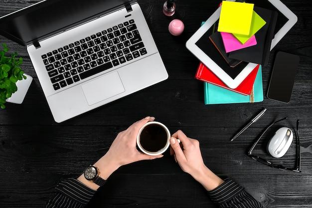 Bovenaanzicht van zakenvrouw werken bij computer op kantoor. plaats voor uw tekst. ideaal voor blog. plat lag op zwarte achtergrond
