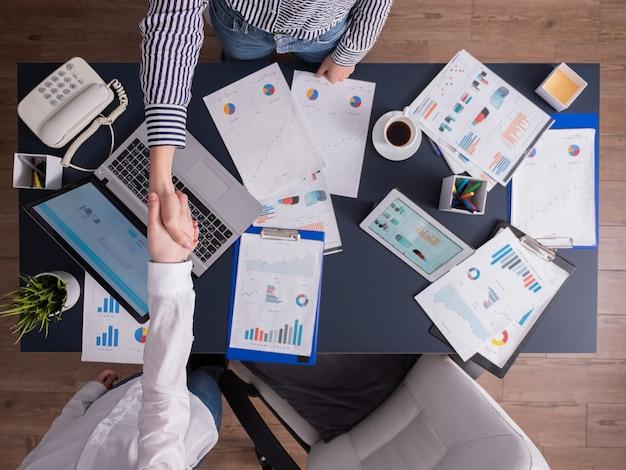 Bovenaanzicht van zakenvrouwen die handen schudden in het hoofdkantoor, aan het bureau zitten, werken in bedrijfsgebouwen. het vieren van het succes van de onderhandelingen over de contractovereenkomst.