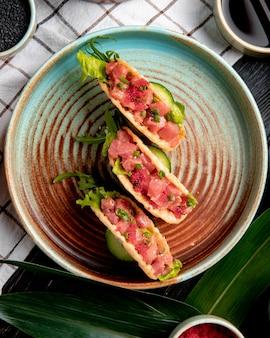Bovenaanzicht van zalm taco's met rode kaviaar en groene ui op een plaat op geruite tafellaken