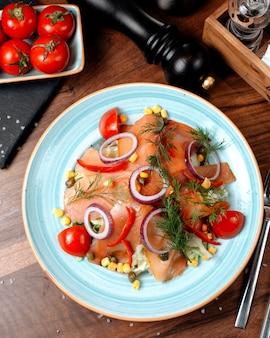 Bovenaanzicht van zalmsalade met rode uien kool en likdoorns gegarneerd met dille in een plaat op houten tafel