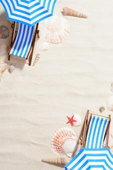Bovenaanzicht van zand in studio met kleine ligbedden en parasols gerangschikt met schelpen