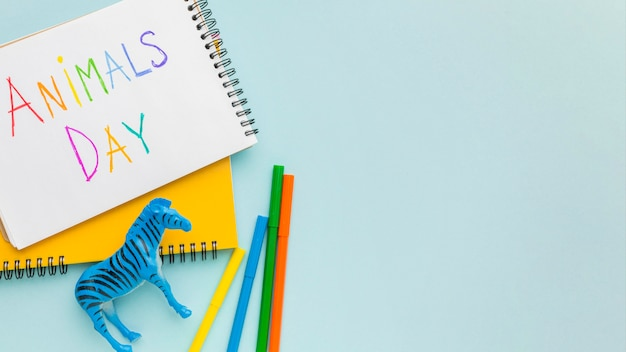 Bovenaanzicht van zebra beeldje en kleurrijk schrijven op notebook met kopie ruimte voor dierendag