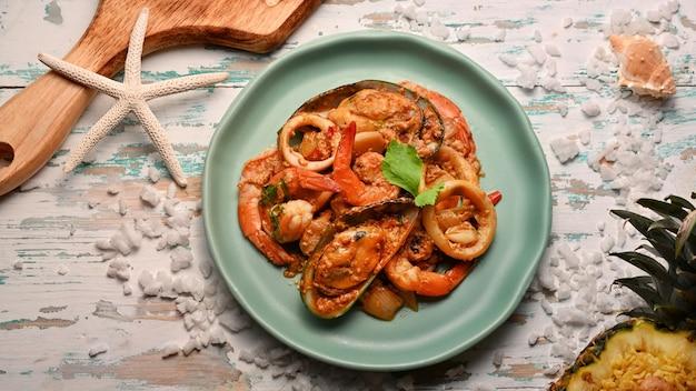 Bovenaanzicht van zeevruchten roergebakken kerriepoeder op groene keramische plaat op houten tafel, thais eten