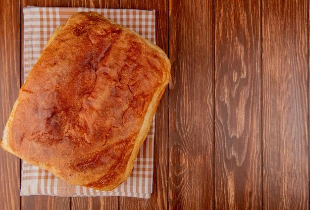 Bovenaanzicht van zelfgebakken brood op plaid doek en houten achtergrond met kopie ruimte
