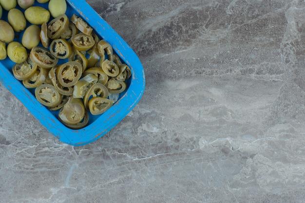 Bovenaanzicht van zelfgemaakte augurk segment en groene olijven op houten plaat.