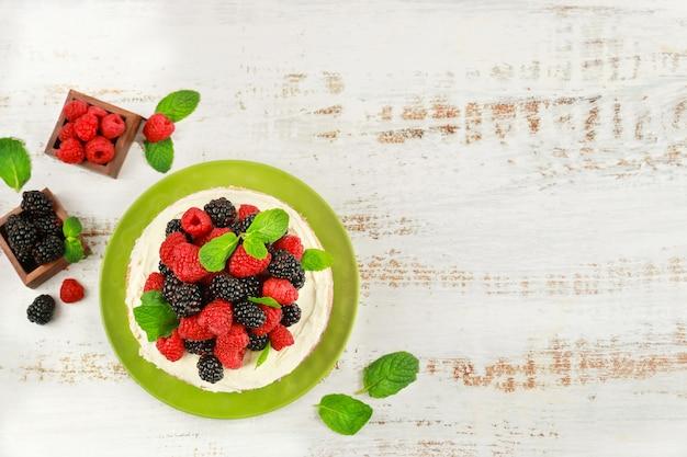 Bovenaanzicht van zelfgemaakte bessencake versierd met verse frambozen en bramen op witte achtergrond.