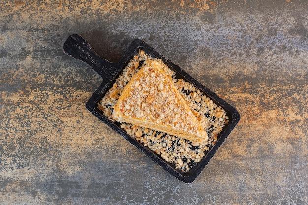 Bovenaanzicht van zelfgemaakte cakeplak op houten bord over rustiek