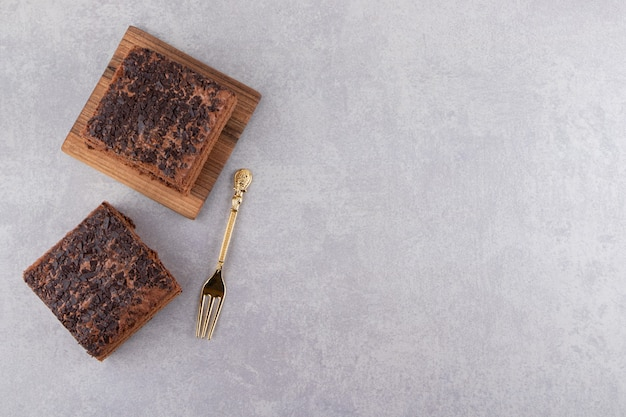 Bovenaanzicht van zelfgemaakte chocolade op houten bord over grijs oppervlak