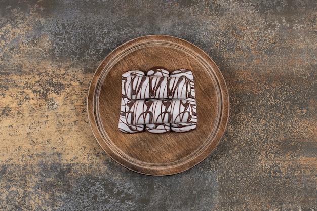 Bovenaanzicht van zelfgemaakte chocoladekoekjes op een houten bord.