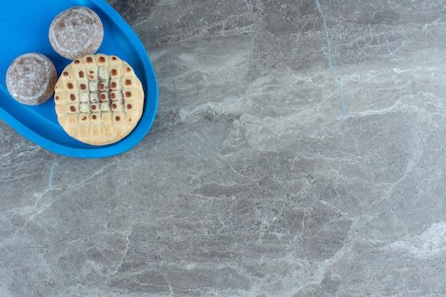 Bovenaanzicht van zelfgemaakte cookie op blauwe houten plaat over grijze achtergrond.