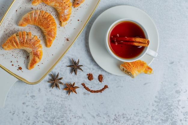 Bovenaanzicht van zelfgemaakte croissants met verse thee op grijze ondergrond.