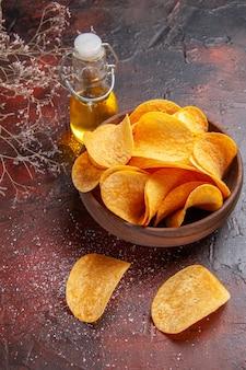 Bovenaanzicht van zelfgemaakte heerlijke knapperige aardappelchips binnen en buiten bruine pot en oliefles op donkere achtergrond