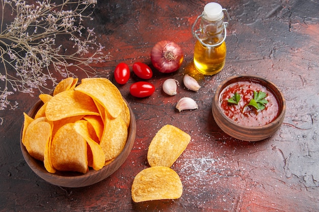 Bovenaanzicht van zelfgemaakte heerlijke knapperige aardappelchips binnen en buiten bruine pot olie fles ketchup tomaten knoflook ui op donkere achtergrond
