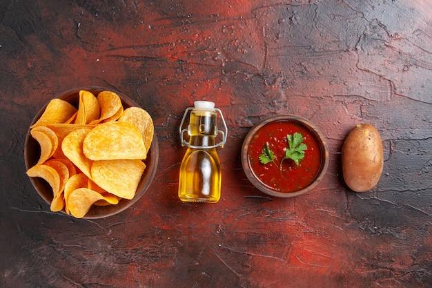 Bovenaanzicht van zelfgemaakte heerlijke knapperige aardappelchips in een bruine pot, gevallen oliefles, ketchup, tomaten, aardappel op donkere achtergrond