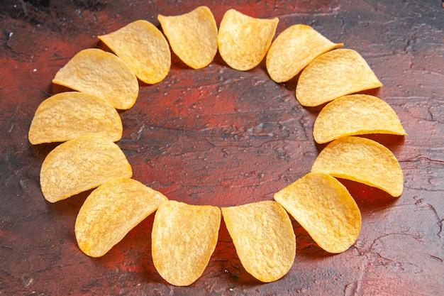 Bovenaanzicht van zelfgemaakte heerlijke knapperige chips op donkere achtergrond met vrije plaats