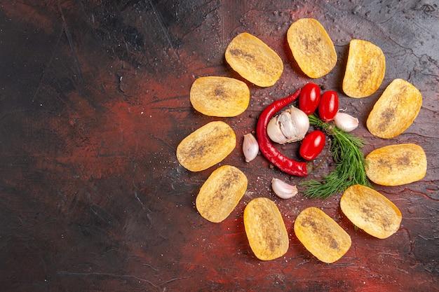 Bovenaanzicht van zelfgemaakte heerlijke knapperige chips rode peper knoflook groene tomaten op donkere tafel