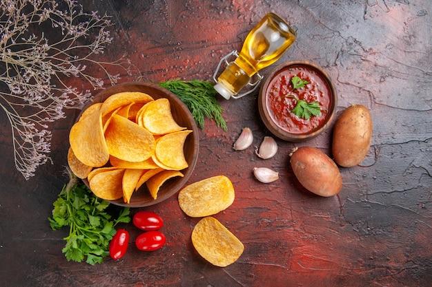Bovenaanzicht van zelfgemaakte heerlijke krokante chips in een kleine bruine kom aardappelen olie fles groene tomaten knoflook en ketchup op donkere achtergrond