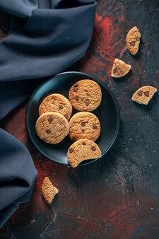 Bovenaanzicht van zelfgemaakte heerlijke suikerkoekjes op zwarte plaat en bloempot op donkere achtergrond van mixkleuren