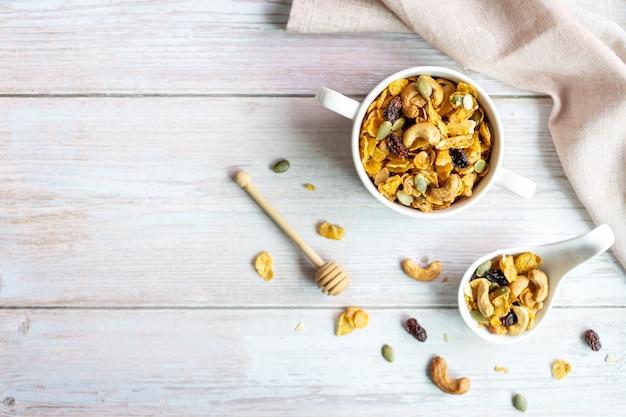Bovenaanzicht van zelfgemaakte honing karamel cornflakes in witte kom met cashewnoten, pompoenpitten en gedroogde rozijnen op wit