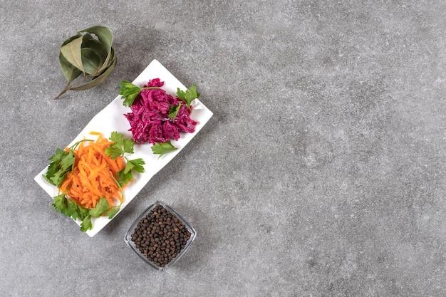 Bovenaanzicht van zelfgemaakte ingeblikte groenten met zwarte peperkorrels op grijze ondergrond.