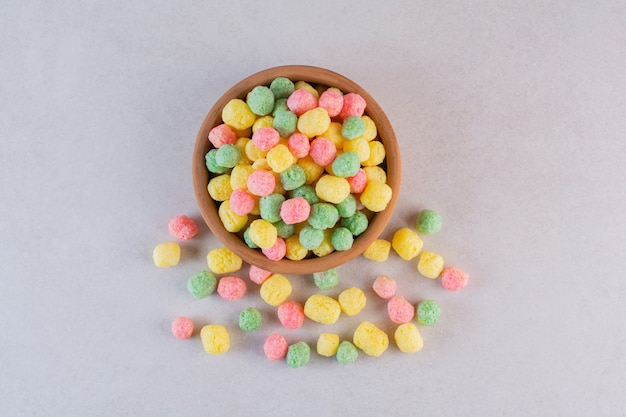 Bovenaanzicht van zelfgemaakte kleurrijke snoepjes in kom over grijs.