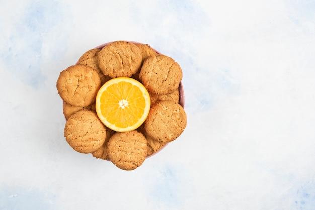 Bovenaanzicht van zelfgemaakte koekjes met half gesneden sinaasappel in kom over witte tafel.